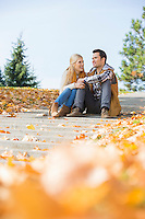 Happy young couple sitting on steps in park