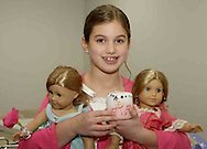 Tara Nix, 8, from Waynesville holds the dolls she brought and the candle she made at the American Girl Tea Party, Saturday, January 27, 2007 in Waynesville's Mary L. Cook Library.