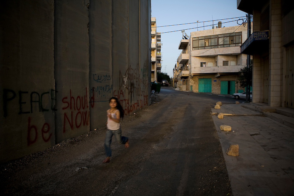 A Palestinian girls runs alongside the security wall in Bethlehem. 14th May 2008