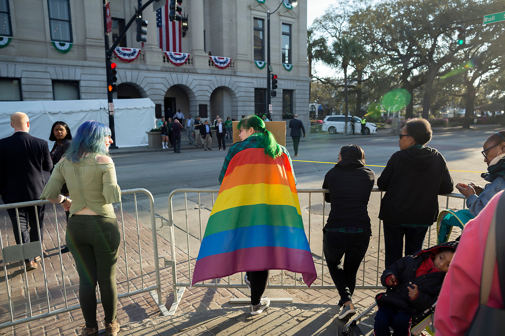 LBGTQ protester Becky Van Heulen wears a gay pride flag near where Vice President Mike Pence will watch the Savannah St. Patrick's Day parade from a balcony at City Hall, Saturday, March 17, 2018, in Savannah, Ga. (AP Photo/Stephen B. Morton)