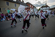 Thaxted Morris Weekend 3-4 June 2017<br /> A meeting of member clubs of the Morris Ring celebrating the 90th anniversary of the founding of the Thaxted Morris Dancing side or team in Thaxted, North West Essex, England UK. <br /> Long man side side perfom in Town Street Thaxted Essex during the early evening mass dancing through the town.<br /> Hundred of Morris dancers from the UK and this year the Silkeborg side from Denmark spend most of Saturday dance outside pubs in nearby villages where much beer is consumed. In the late afternoon all the sides congregate in Thaxted where massed dancing is perfomed along Town Street. As darkness falls across Thaxted the spell binding Abbots Bromley Horn Dance is performed to the sound of a solo violin in the dark.