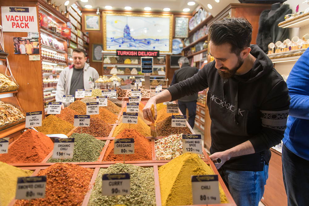 Male merchant uses paint brush to tidy up excess spices off of container in his spice shop at Istanbul Spice bazaar in Turkey