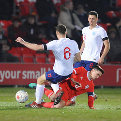 19/3/2019 - Aaron Edwards (TNS) slides in on Josh Taylor (Sutton) during the C International between England and Wales at the Peninsula Stadium, Salford.<br /> <br /> Pic: Mike Sheridan/County Times<br /> MS023-2019