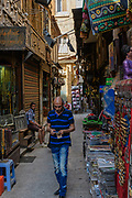 Potential customer walks past an Egyptian vendor as he waits  patiently for customers in his shop in Khan Al-Khalili market