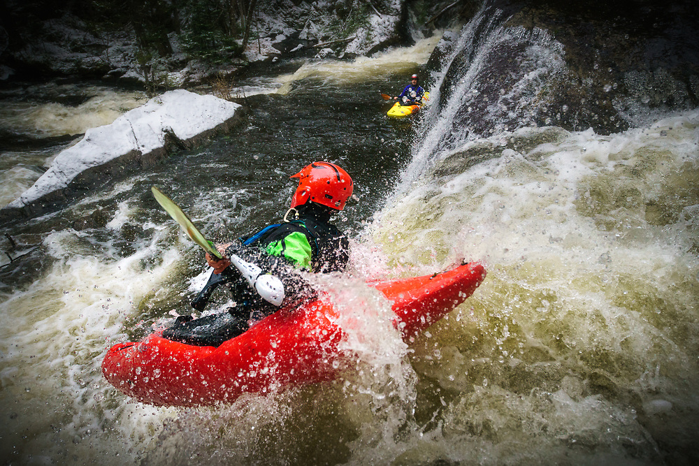 A kayaker launches over a 15 foot waterfall while running the Green River in northern Vermont