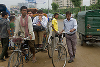 Young Indian executives going to work by rickshaw in Gurgaon, New Delhi's CBD.