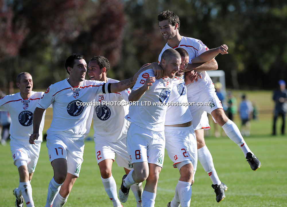 Waitakere's Brent Fisher celebrates with team mates after scoring a goal in the final minute to qualify for the final.<br />