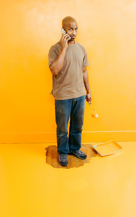 A mid 30's African American man surrounded by wet paint, holding a paint roller, and talking on a cell phone...Model release:20060425_MR_A