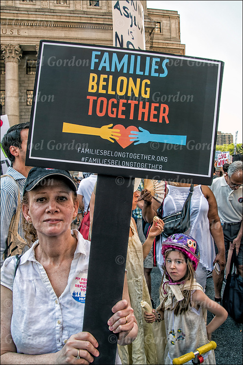 Protester holding up sign &quot;Families Belong Together&quot;  @ Foley Square and then across the Brooklyn Bridge before rallying in Cadman Plaza.<br /> <br /> Thousands are gathering in Manhattan &mdash; in one of about 750 planned marches around the country &mdash; to protest the Trump administration&rsquo;s rescinded policy of separating immigrant children and parents suspected of illegally crossing the U.S. border. <br /> <br /> Demand an end to President Trump&rsquo;s cruel &ldquo;zero tolerance&rdquo; policy and to support immigrant families in New York and across the country.<br /> <br /> Every day, this administration threatens the very future of our communities. The conditions these children are being subjected to is deplorable and un-American.