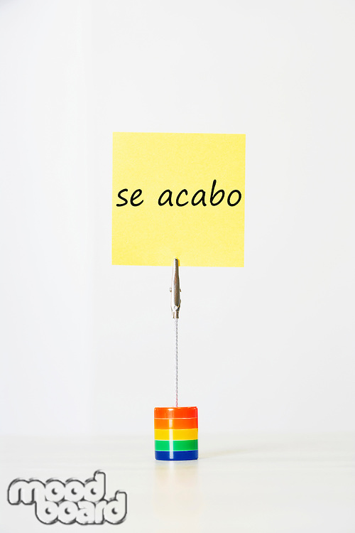 Sticky notepaper with Spanish text meaning It's over clipped to a multicolored card holder