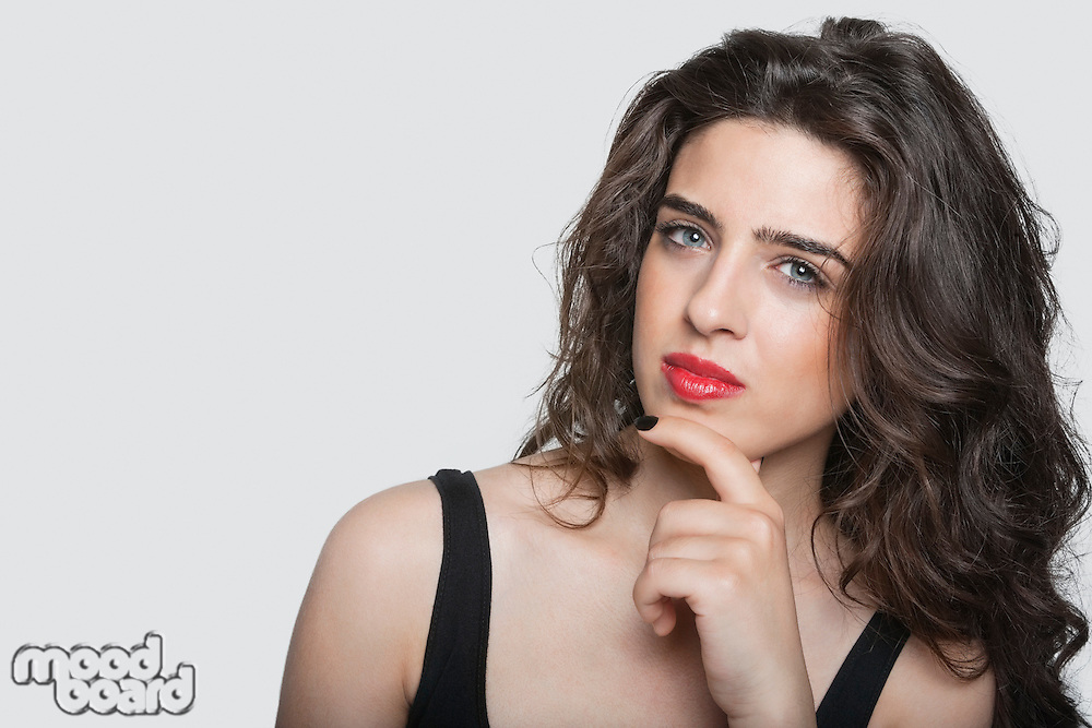 Portrait of a thoughtful young woman with hand on chin over gray background