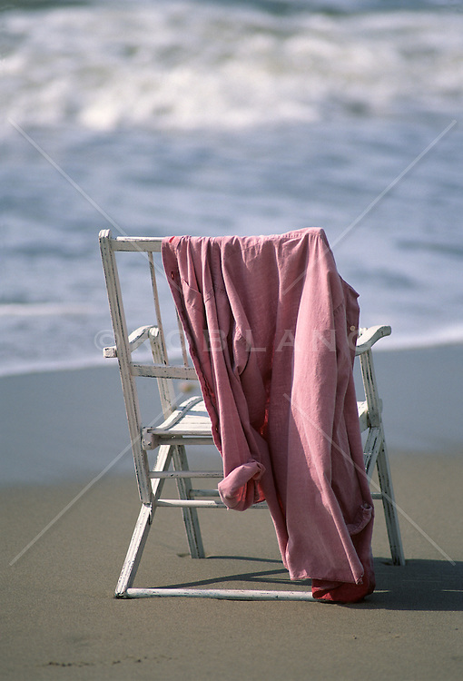 chair at the beach with a shirt hanging over the back