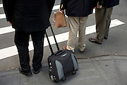 businessmen with various briefcases waiting to cross the street