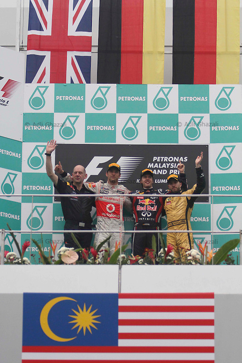 Second-placed McLaren-Mercedes driver Jenson Button (L) of Britain and third-placed Lotus-Renault driver Nick Heidfeld of Germany (R) pose with winner Red Bull-Renault driver Sebastien Vettel (C) of Germany on the podium after the Formula One Malaysian Grand Prix in Sepang on April 10, 2011.