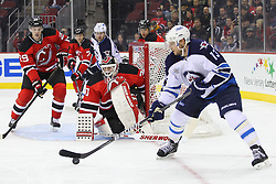 Jan 17; Newark, NJ, USA; New Jersey Devils goalie Martin Brodeur (30) watches Winnipeg Jets center Kyle Wellwood (13) skate with the puck by his goal during the first period at the Prudential Center.