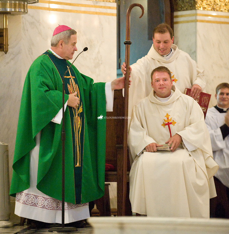 Father William Vatterott  was installed as the 8th Pastor of St. Cecilia's Parish in South St. Louis on Sunday, September 13.  The congregation cheered applause and Fr. Vatterott sits with a smile after Archbishop Robert Carlson's blessing.   The Archbishop hands his crozier to his Secretary Fr. Brian Fischer.