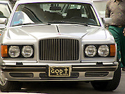 A Rolls Royce with a religious message on the front number plate