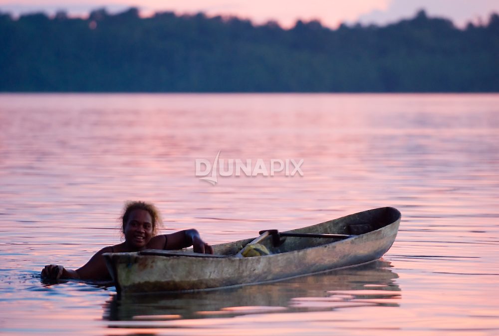 A woman off-loads oysters collected in preparation for a funeral feast while enjoying a spectacular Kia sunset.
