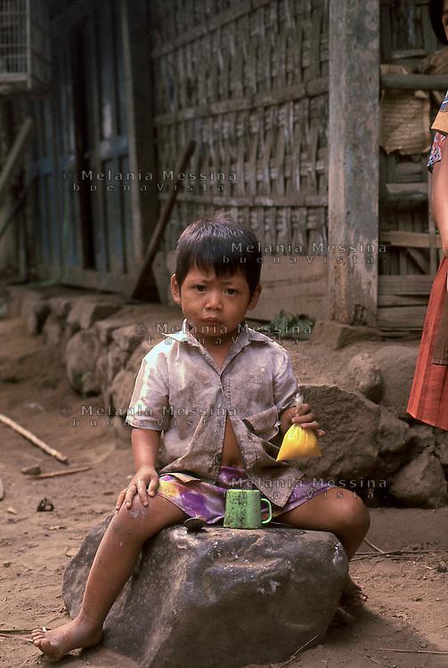 Indonesia, Java island: a child ready to drink his jamu (herbal medicine).<br /> Indonesia; Giava: un bambino con il suo jamu ( drink a base di erbe mediche).