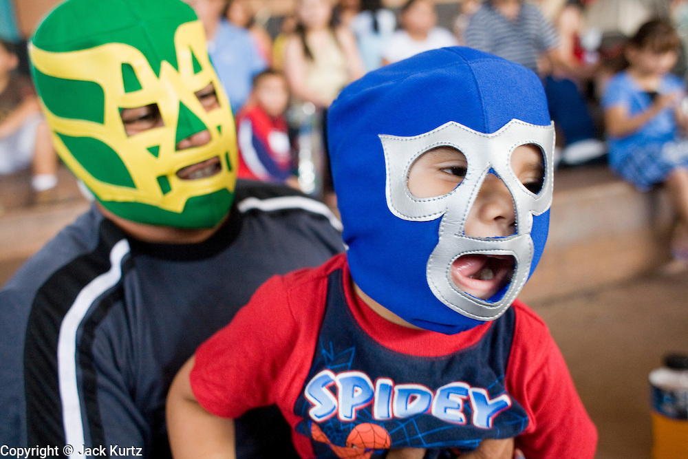 13 JULY 2008 -- PHOENIX, AZ: A father holds his son in his lap at a Lucha Libre show in Phoenix. Lucha Libre is Mexican style wrestling. There are heros (Tecnicos) and villians (Rudos). The masks are popular as children's gifts and tourist mementos. As the size of the Mexican community in the Phoenix area has grown, attendance at the Lucha Libre shows has increased. Lucha Libre differs from American style entertainment wrestling in several ways, but principally the wrestlers are more acrobatic and rely less on body slams than American wrestling. The shows, which used to be held only periodically, are now held every week at El Gran Mercado, a flea market and swap meet that caters mostly to the Mexican community in Phoenix.  PHOTO BY JACK KURTZ