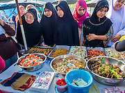18 JUNE 2015 - PATTANI, PATTANI, THAILAND:   Muslim women shop in the Pattani Ramadan Bazaar. People come to the street food market late in the day to buy meals for the evening Iftar meal, which breaks the day long fast. Ramadan is the ninth month of the Islamic calendar, and is observed by Muslims worldwide as a month of fasting to commemorate the first revelation of the Quran to Muhammad according to Islamic belief. This annual observance is regarded as one of the Five Pillars of Islam. Islam is the second largest religion in Thailand. Pattani, along with Narathiwat and Yala provinces, all on the Malaysian border, have a Muslim majority.       PHOTO BY JACK KURTZ