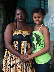 Carmen Suyapa stands with her daughter Brithany, 13, in front of their home. Carmen is HIV-positive and says that Brithany helps her remember when to take her pills each day. She says that it is important for her to be public with her diagnosis in order to help fight ignorance and stigma,