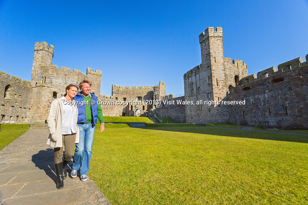 Couple walking in castle<br /> Caernarfon Castle <br /> Cadw Sites<br /> World Heritage Sites<br /> SAMN: CN079<br /> NGR: SH477626<br /> Gwynedd<br /> North<br /> Castles<br /> Medieval<br /> Defence<br /> Historic Sites