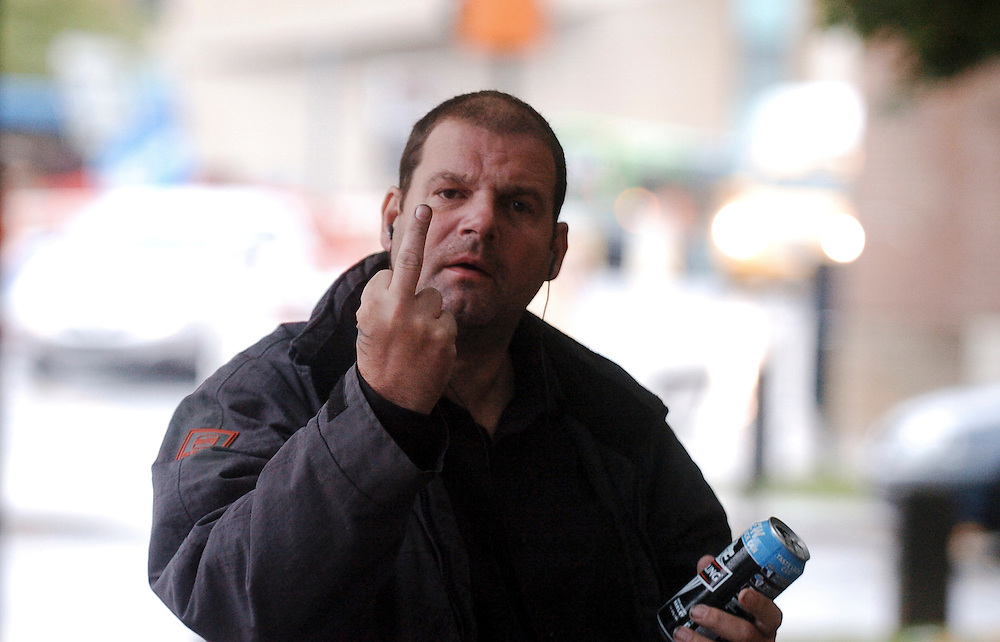 Outside Derby Crown Court, a man shows me the middle finger as I take his photograph