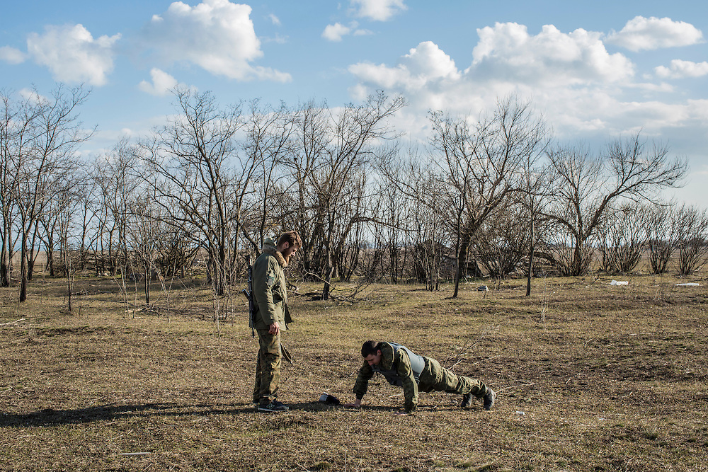 Alex, left, a drill sergeant, doles out push-ups as punishment to a member of the Azov Brigade during weapons training at one of the group's training grounds on Saturday, March 7, 2015 in Kulykivske, Ukraine. Photo by Brendan Hoffman, Freelance