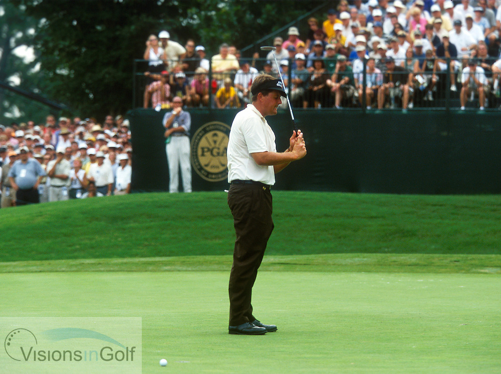 Phil Mickelson bops himself with his putter after a missed putt on #16.<br />