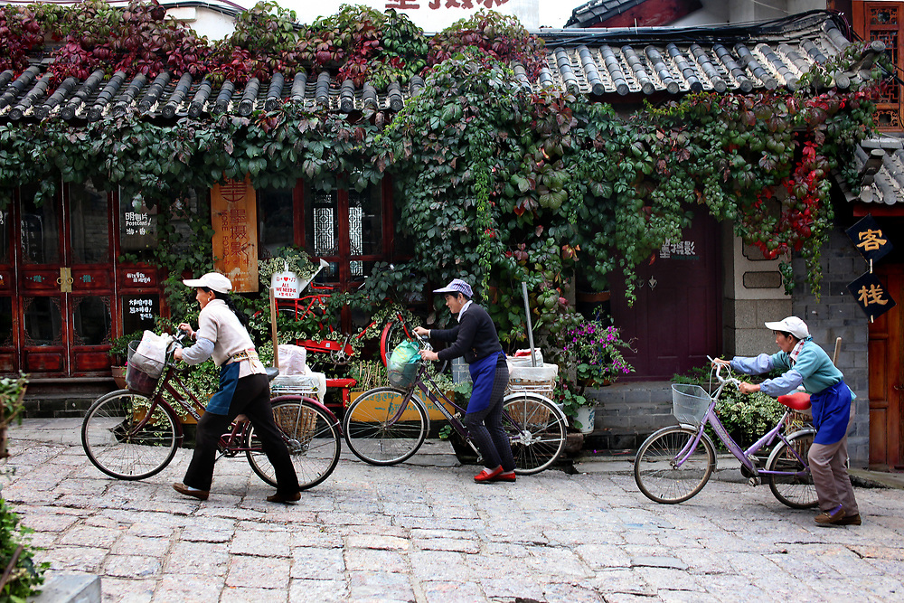 Bike riders in old-town Lijiang,Yunnan, China; September, 2013.