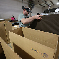 Truman Dulaney begins packing completed dog beds so they can be shipped to Bed Bath & Beyond stores across the country.
