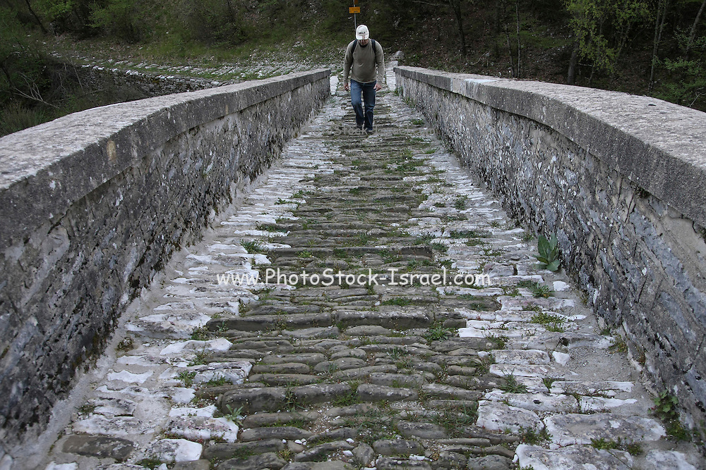 Greece, Epirus, Zagori, Pindus Mountains, Tourist walking across an old disused Arched Stone Bridge