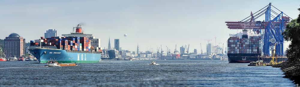 Panorama von Hamburg mit Landungsbrücken, Docklands, Blohm und Voss und Elbphilharmonie. Ein Container-Schiff fährt auf der Elbe Richtung Nordsee, ein anderes steht am Terminal Burchardkai zum Be- und Entladen.