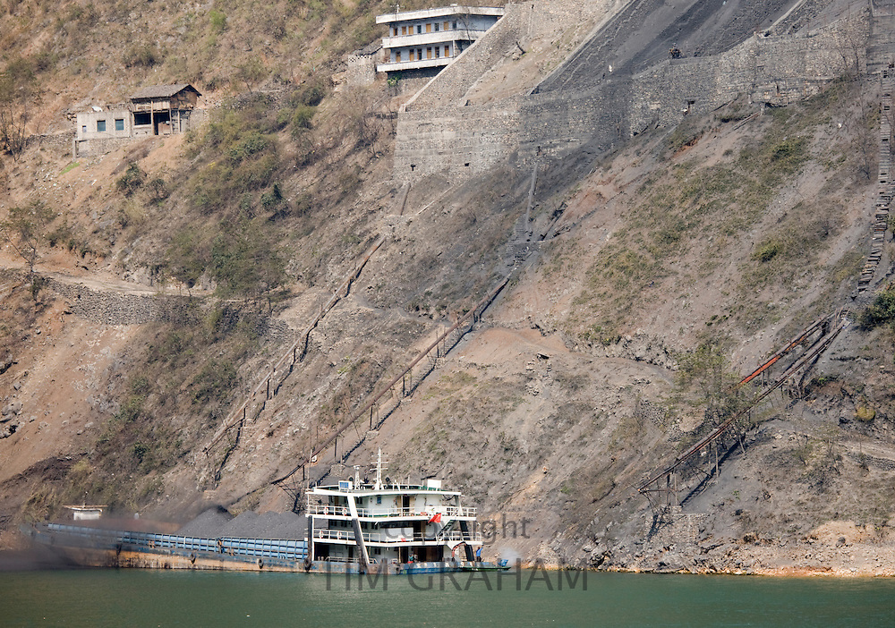 Coal slides down hillside to fill freight ship, in Three Gorges area, Yangtze River, China