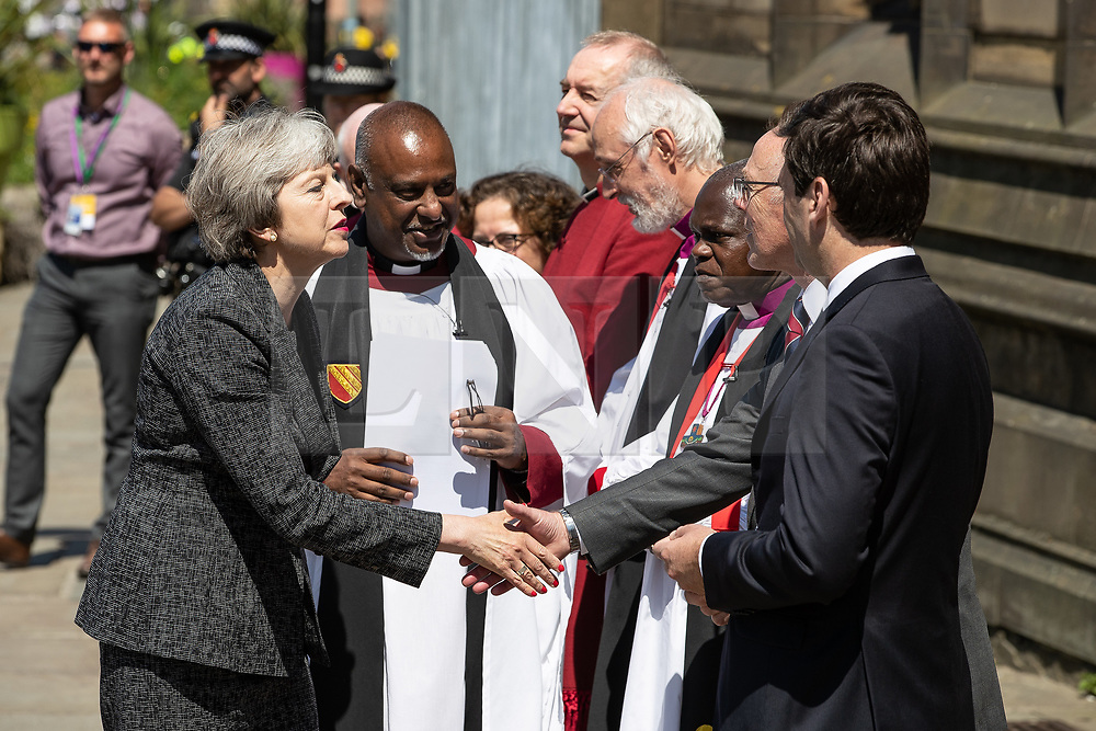 © Licensed to London News Pictures . 22/05/2018 . Manchester , UK . Prime Minister THERESA MAY is greeted by dignitaries , including Bishop DAVID WALKER  JOHN SENTAMU , SIR RICHARD LEESE (shaking hands)and ANDY BURNHAM , wait to receive guests at Manchester Cathedral ahead of a Service of Remembrance on the first anniversary of the Manchester Arena bombing . On the evening of 22nd May 2017 , Salman Abedi murdered 22 people and seriously injured dozens more , when he exploded a bomb in the  foyer of the Manchester Arena as concert-goers were leaving an Ariana Grande gig . Photo credit : Joel Goodman/LNP