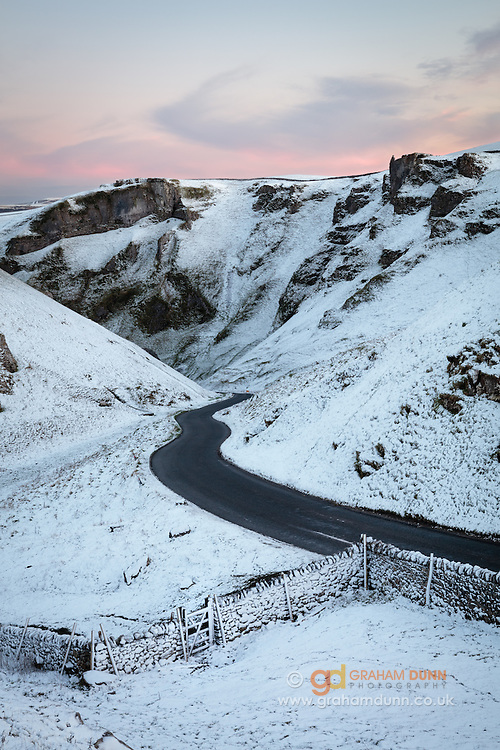 A light covering of snow defines the winding road as it leads into Winnats Pass in the Peak District. English landscape photography in Derbyshire. Winter, January, 2016.
