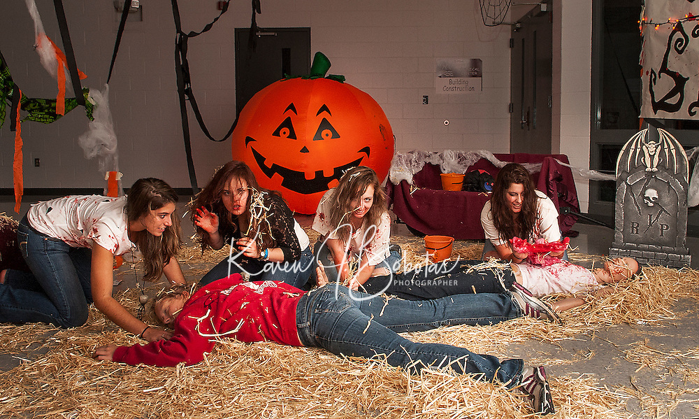 """Andrea Selesky, Gwen Huot, Brianna Healey, Haven Gilbert and Hannah Forston (as the dead body) represent the senior class for their """"Halloween"""" themed hallway during Homecoming festivities moved indoors due to the inclement weather Friday evening.  (Karen Bobotas/for the Laconia Daily Sun)"""