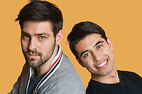 Portrait of a young male friends back to back over colored background