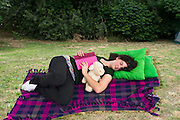 Young teen falls asleep on a blanket in a park while reading a book