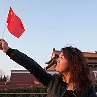 China, Beijing, Young woman holds Chinese flag near portrait of Chairman Mao Zedong at entrance to Forbidden City at sunset on spring evening