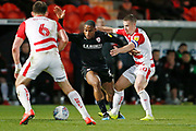 Barnsley forward Victor Adeboyejo (29) goes pastTommy Rowe of Doncaster Rovers  during the EFL Sky Bet League 1 match between Doncaster Rovers and Barnsley at the Keepmoat Stadium, Doncaster, England on 15 March 2019.