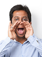 Portrait of young Indian man shouting against white background