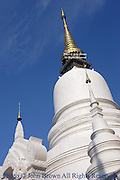 A beautiful white Buddhist stupa stands in the afternoon sun at a temple in Chiang Mai, Thailand.