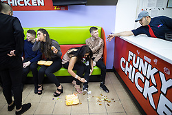 """© Licensed to London News Pictures . 24/12/2016 . Manchester , UK . A woman cleans spilled takeaway food from a man's clothes inside Funky Chicken takeaway . Revellers out in Manchester City Centre overnight during 2016's second """" Mad Friday """" , named for historically being one of the busiest nights of the year for the emergency services in the UK . Photo credit : Joel Goodman/LNP"""