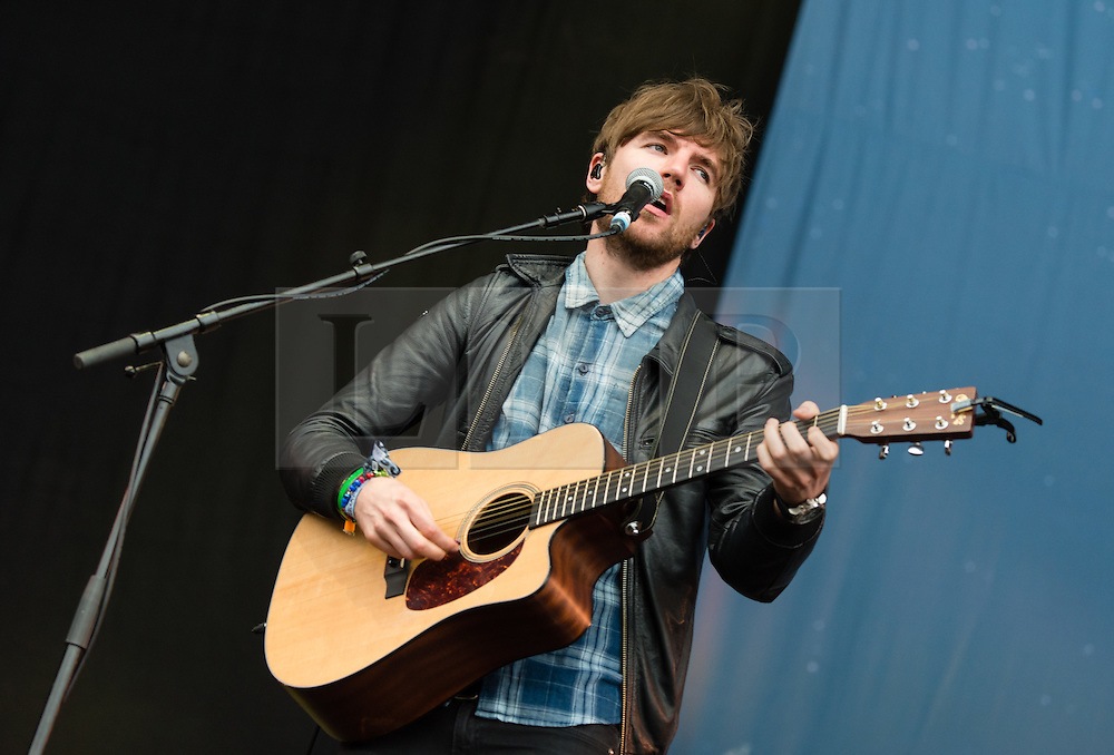 © Licensed to London News Pictures. 12/06/2015. Newport, UK.   Kodaline performing live at Isle of Wight Festival 2015, Day 2 Friday.  In this picture - Mark Prendergast.  This afternoon has seen torrential downpours of rain after the last day of hot sunshine.   Photo credit : Richard Isaac/LNP
