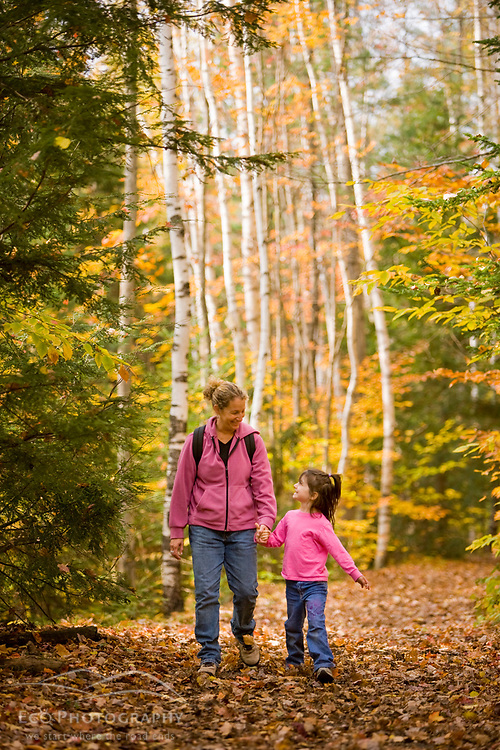 A mom and her young daughter (age 6) hike on the Lincoln Woods Trail in New Hampshire's White Mountain National Forest.