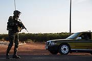 BANJUL, GAMBIA - JAN 22: An ECOWAS soldier checks traffic ahead of entering Banjul on 22 January 2017 in Banjul, Gambia.