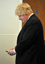 © Licensed to London News Pictures. 01/02/2012, London, UK. BORIS JOHNSON checks his mobile phone.  Boris Johnson and Fire Minister Bob Neill, MP open the centre. The opening of a state of the art new fire control centre ahead of the London 2012 Olympic and Paralympic Games. The London Operations Centre (LOC) brings together in a secure, bomb proof building London Fire Brigade's control centre, London's emergency planning teams and by April the National Co-ordination Centre.Photo credit : Stephen Simpson/LNP