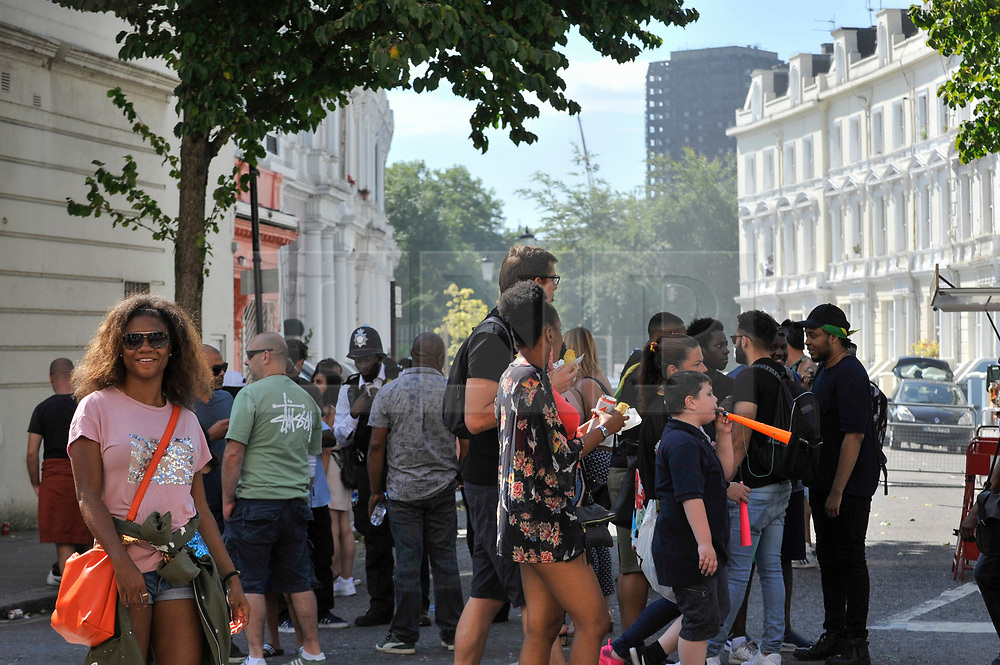 © Licensed to London News Pictures. 27/08/2017. London, UK. The burned out shell of Grenfell Tower looks down on members of the public enjoying Family Day at the Notting Hill Carnival.  Over one million revellers are expected to attend Europe's biggest street party which takes place over the Bank Holiday Weekend. Photo credit : Stephen Chung/LNP